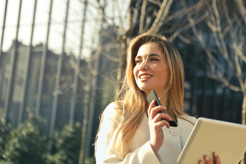 uśmiechnięta kobieta otrzymuje telefon, żedostała pracę