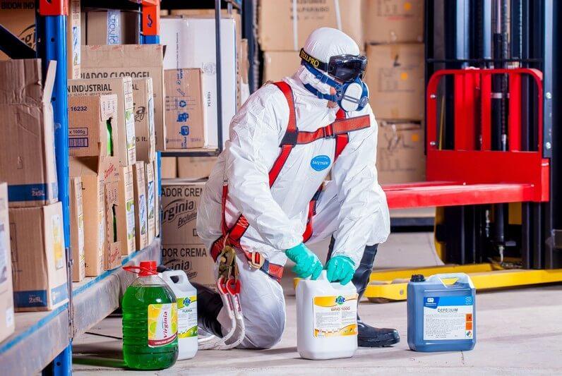 pracownik ubrany wśrodki ochrony indywidualnej pracuje zproduktami chemicznymi