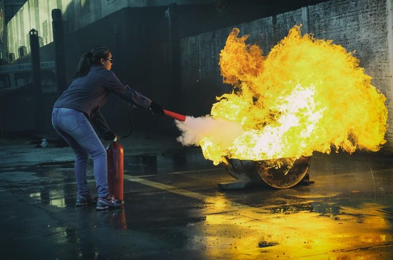 Szkolenie inspektorów ochrony przeciwpożarowej kobieta gasi pożar gaśnicą