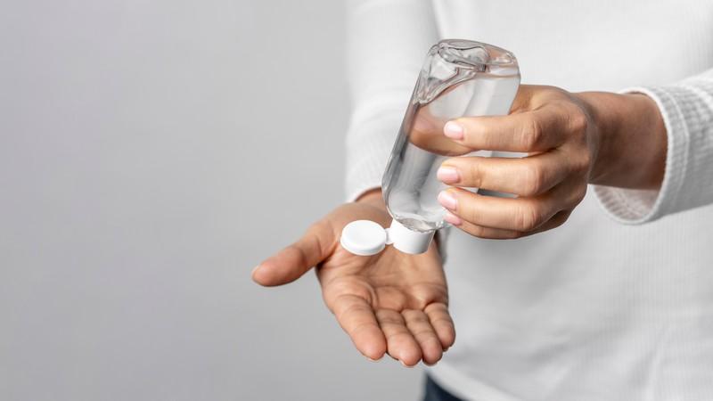 pomysły nawalkę zkoronawirusem - mężczyzna dozujący środek dezynfekujący nadłoń
