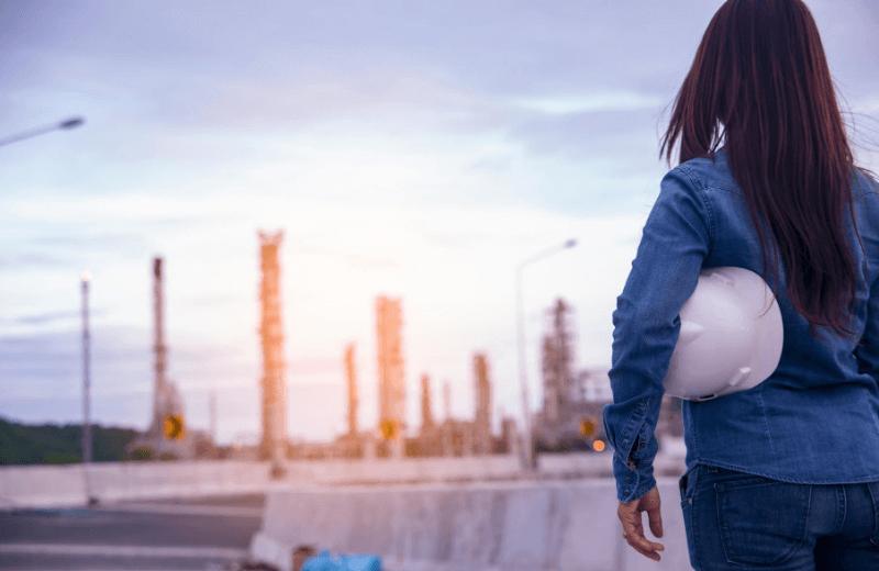 Plusy iminusy pracy wsłużbie BHP - kobieta zkaskiem natle fabryki