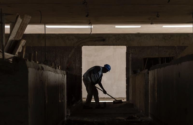 Praca wpojedynkę iobowiązek meldowania się - widok pracownika pracującego samodzielnie wpomieszczeniu pracy
