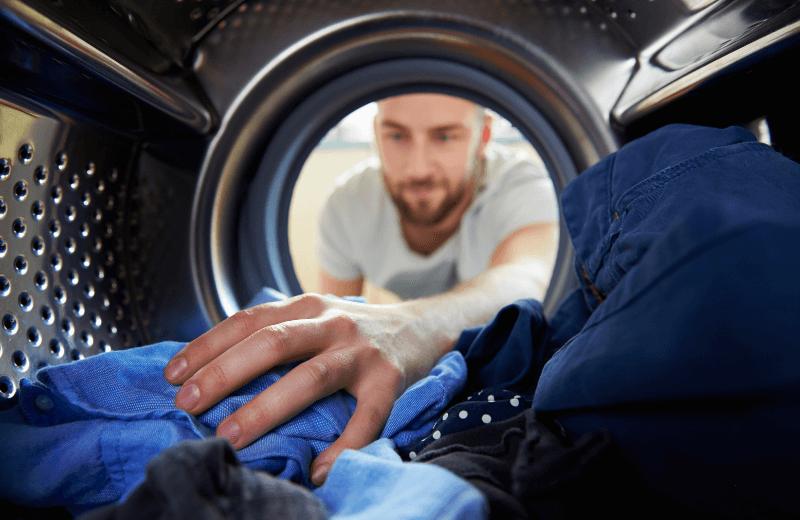 ekwiwalent zapranie odzieży roboczej - mężczyzna wkładający odzież dopralki
